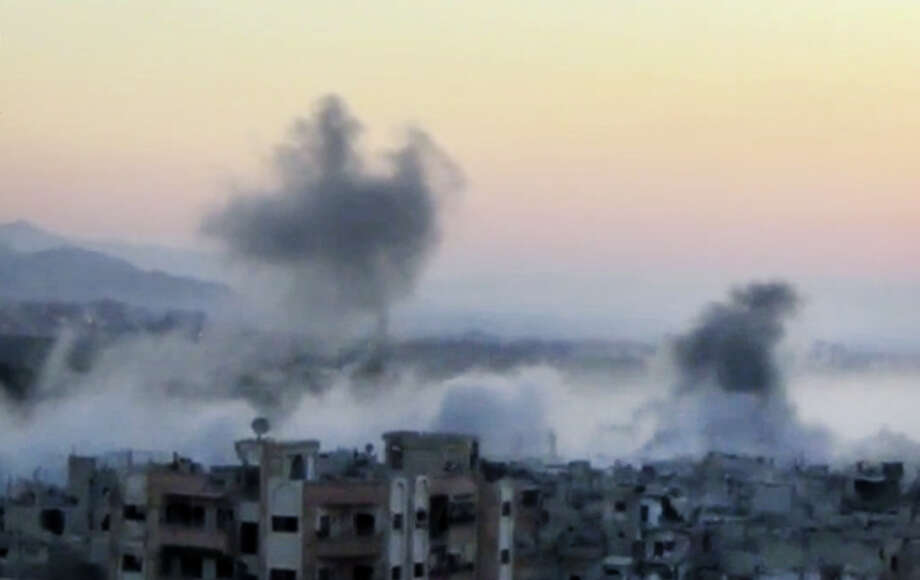 In this image taken from video obtained from the Shaam News Network, which has been authenticated based on its contents and other AP reporting, smoke rises from buildings due to heavy artillery shelling in Barzeh, a district of Damascus, Syria, Tuesday, Sept. 10, 2013. Photo: AP