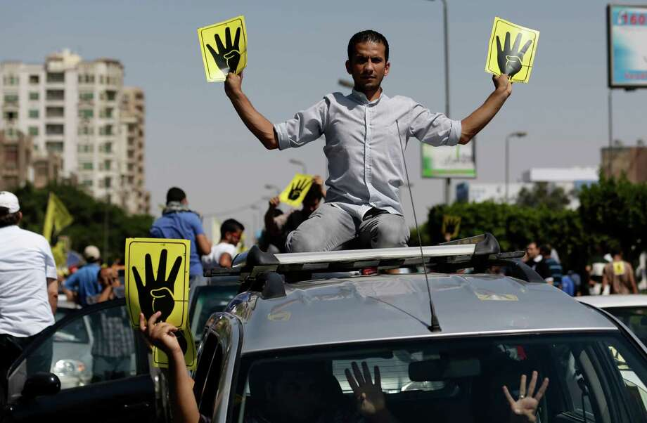 Supporters of Egypt's ousted President Mohammed Morsi chant slogans and hold placards showing an open palm with four raised fingers, which has become a symbol of the Rabaah al-Adawiya mosque, where Morsi supporters had held a sit-in for weeks that was violently dispersed in August during a protest in Cairo, Egypt, Friday, Sept. 13, 2013. Sporadic clashes have erupted in several cities across Egypt as supporters of the toppled Islamist president continue to hold protests. Photo: AP