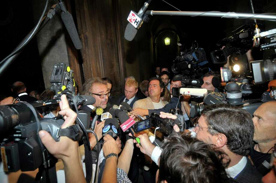 Senator Mario Michele Giarrusso, center, is mobbed by media upon arrival for the second meeting of an Italian Senate panel working on the decision whether ex-Premier Silvio Berlusconi should lose his seat in the upper chamber of Parliament because of his tax fraud conviction and prison sentence, in Rome Tuesday, Sept. 10, 2013.  Berlusconi has threatened to yank his ministers out of Premier Enrico Letta's unusual left-right coalition if his fellow senators vote to strip him of his seat. The Senate action is based on a 2012 law stipulating that anyone convicted to more than two years in prison cannot hold or run for office for six years. (AP Photo/Lapresse) ITALY OUT Photo: AP