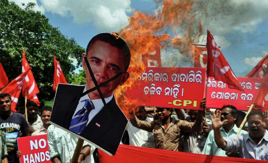 "Activists of Communist Party of India (CPI) burn an effigy representing U.S. President Barack Obama during a protest against a possible U.S.-led attack on Syria, in Bhubaneswar, India, Friday, Sept. 13, 2013.  Banner in the background reads, ""America will not be allowed to dominate"". Photo: AP"