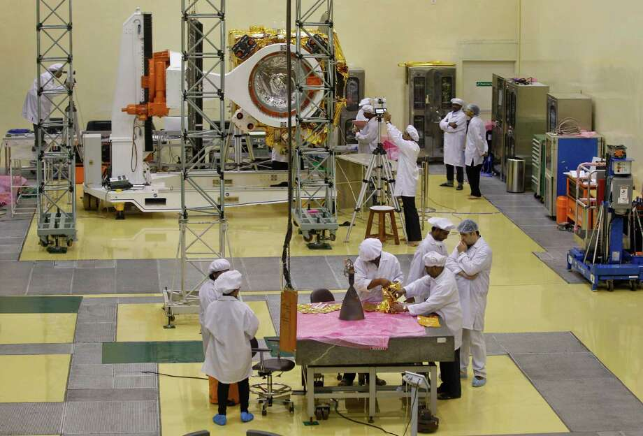 Indian engineers work with their staff next to a pyramid shaped rocket or Liquid Apogee Motor, foreground, to be installed on the Mars orbiter spacecraft, background, at the satellite center of Indian Space Research Organization (ISRO) in Bangalore, India, Wednesday, Sept. 11, 2013. India�s ambitious USD $71,096,068 Mars orbiter mission is scheduled to be launched by Polar Satellite Launch Vehicle (PSLV-C25) between Oct. 21 and Nov. 19, 2013 from Sriharikota in south India, project director Arunan. S said Wednesday. Photo: AP