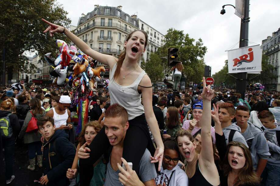 Partygoers dance on the Bastille Plaza during the annual Techno parade in the streets of Paris, Saturday, Sept. 14, 2013. Photo: AP