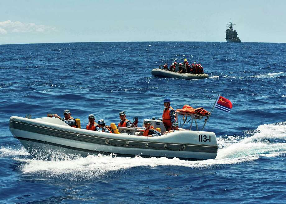In this photo provided by the U.S. Navy, Chinese People's Liberation Army-Navy sailors and U.S. Navy sailors in inflatable boats work together during a search and rescue exercise off the coast of Honolulu on Monday, Sept. 9, 2013. Three Chinese ships carrying hundreds of sailors came to Hawaii for a rare visit intended to foster familiarity between the two navies. Photo: AP