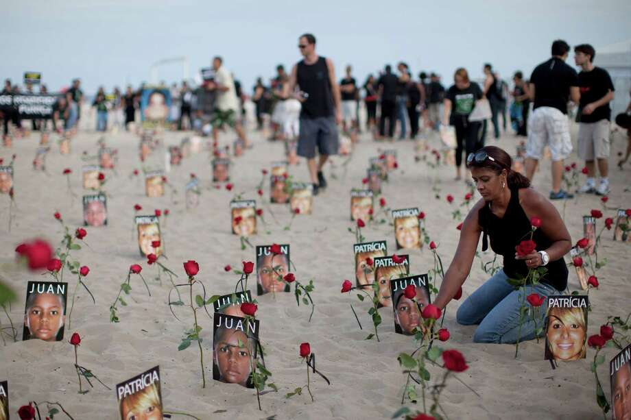 FILE - In this July 31, 2011 file photo, a woman places a flower on the beach in front of a photograph of Juan Moraes who was killed during a police operation, during protest against impunity in Rio de Janeiro, Brazil. On Friday, Sept. 13, 2013, a Brazilian court announced it has sentenced four Brazilian police officers to more than 30 years in prison for the killing of the 11-year old boy during a shootout in the Danon slum. Photo: AP
