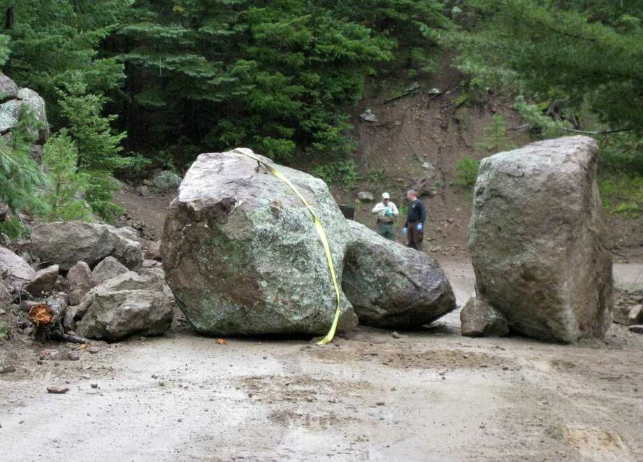 This photo released Wednesday Sept. 11, 2013 by Coconino County Sheriff's office shows investigators at the scene of a boulder slide where a Phoenix man was seriously injured while trying to move another boulder. The 27-year-old unidentified man was hospitalized for injuries to his legs and pelvis. Photo: AP