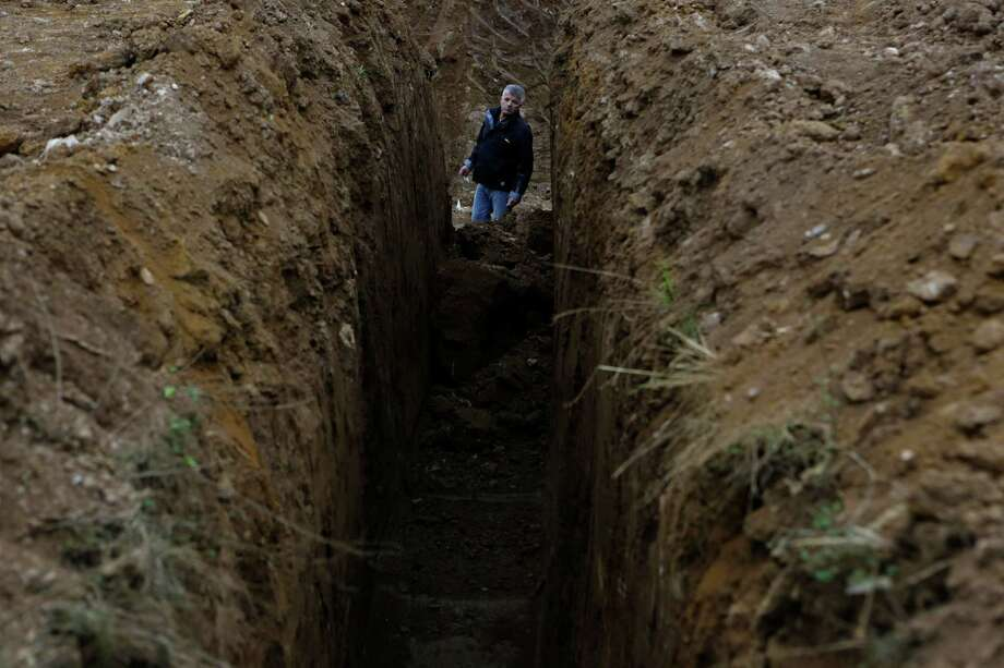 Bosnian forensic worker Huskic Suad searches for human remains at a mass grave site near the Bosnian town of Prijedor, on Wednesday, Sept. 11, 2013.  Forensic experts have unearthed the remains of ten people so far, but believe there are many more yet undiscovered as they excavate a 7 meters deep trench to find the remains of Bosniaks and Croats killed by Serb forces during their campaign to eliminate all non-Serbs from parts of the country they controlled during the 1992-95 Bosnian war.  Authorities are still searching for 1,200 Bosniaks and Croats missing from the area of Prijedor. Photo: AP