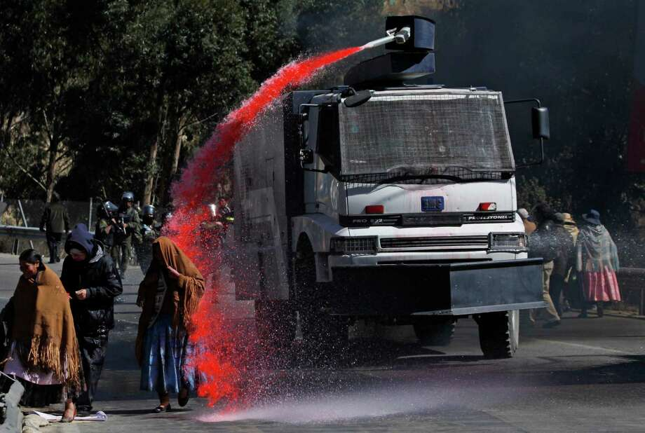 Police spray red stained water at demonstrators to break up their road block in La Paz, Bolivia, Wednesday, Sept. 11, 2013.  Citizens are upset that the latest national census reduces the city's population by 30,000, stripping it of millions in annual funding from the central government. Photo: AP