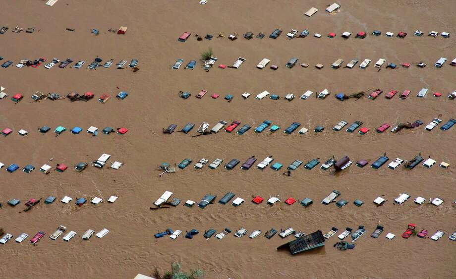 A field of parked cars and trucks sits partially submerged near Greeley, Colo., Saturday, Sept. 14, 2013, as debris-filled rivers flooded into towns and farms miles from the Rockies. Hundreds of roads, farms and businesses in the area have been damaged or destroyed by the floodwaters. Photo: AP