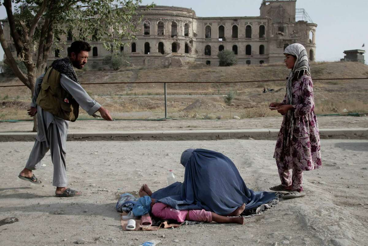 A man gives some money to an Afghan woman sitting on the ground by the palace of the late King Amanullah Khan, which was destroyed during the civil war in early 1990s, in Kabul, Afghanistan, Friday, Sept. 13, 2013.