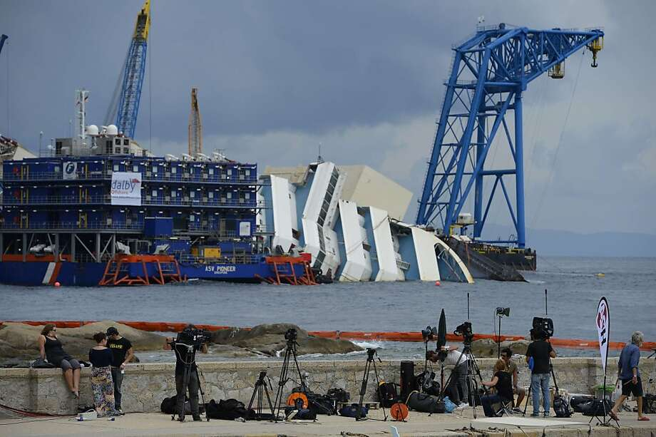 """TOPSHOTS A general view shows journalists working with the wreck of Italy's Costa Concordia cruise ship in the background, near the harbour of Giglio Porto on September 15, 2013. Salvage workers will attempt to raise the cruise ship on September 16, 2013, weather permitting, in the largest and most expensive maritime salvage operation in history, so-called """"parbuckling"""", to rotated the ship by a series of cables and hydraulic machines. Thirty-two people died when the ship, with 4,200 passengers onboard, hit rocks and ran aground off the island of Giglio on January 2012.   AFP PHOTO / ANDREAS SOLAROANDREAS SOLARO/AFP/Getty Images Photo: Andreas Solaro, AFP/Getty Images"""