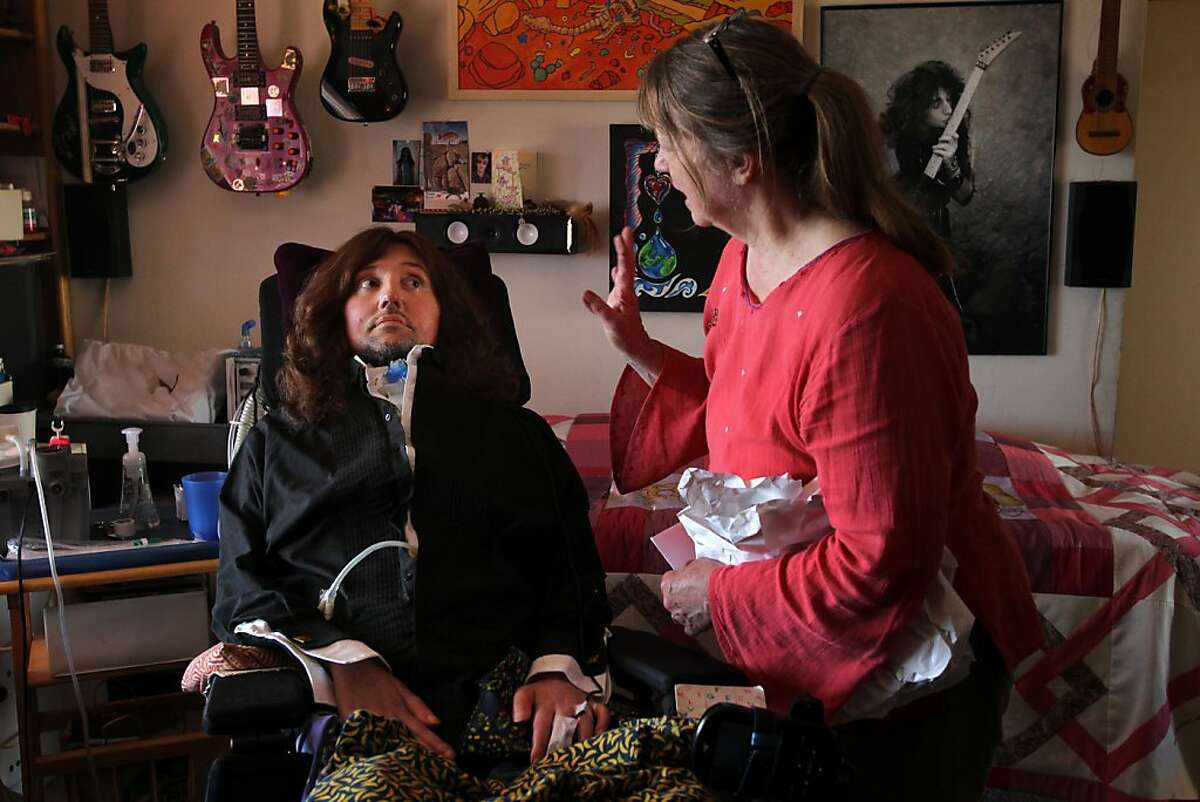 Pat Becker, right, mother of Jason Becker, left, waves goodbye to Jason September 14, 2013 at Becker's home in Richmond, Calif. Becker had already recorded two full length albums before the age of 21 and had just been selected to play guitar for David Lee Roth when he was diagnosed with Amyotrophic Lateral Sclerosis or ALS and given only years to live. Becker is now confined to a wheelchair without the ability to move or speak. However, with the help of a communication system invented by his father, Gary, in 1996, wherein he only uses his eyes, Becker is still able to compose music and collaborate with other artists.