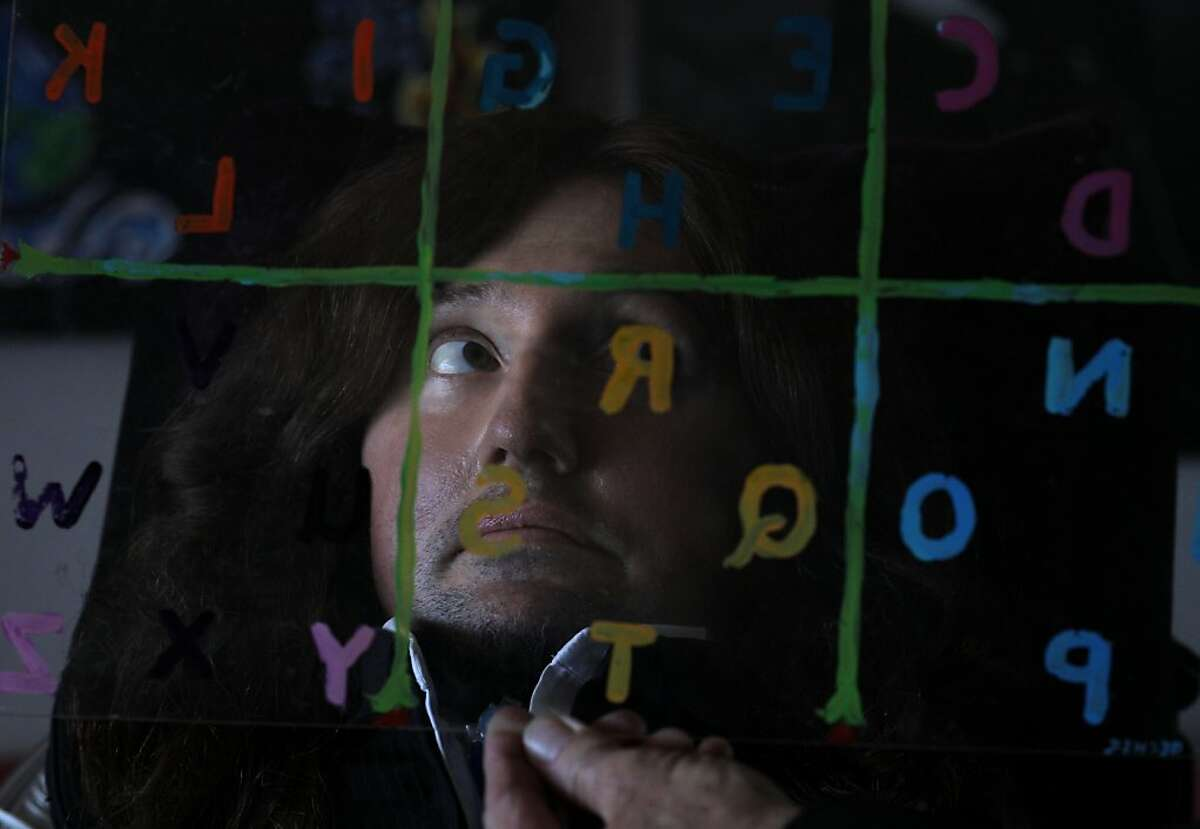 Jason Becker's father, Gary, right, demonstrates the speaking system he invented for Becker in 1996, center, in which he only uses his eyes to make words by moving them to each