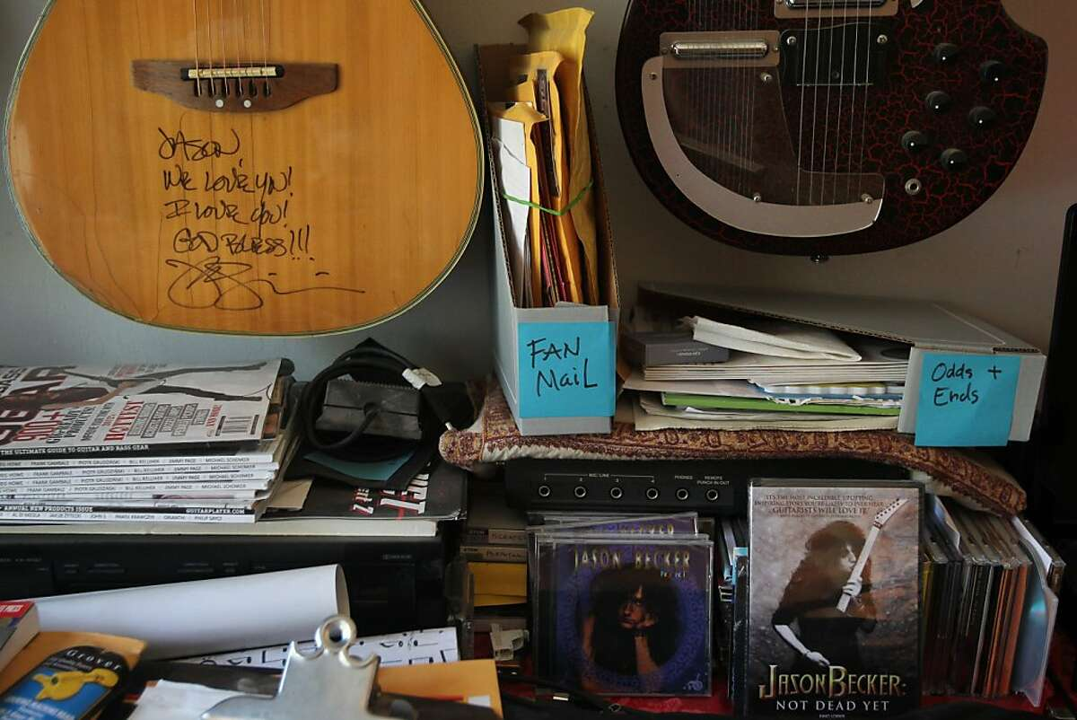 Various items, including donated guitars, fan mail and old albums line a desk in Jason Becker's home September 14, 2013 in Richmond, Calif. Becker had already recorded two full length albums before the age of 21 and had just been selected to play guitar for David Lee Roth when he was diagnosed with Amyotrophic Lateral Sclerosis or ALS and given only years to live. Becker is now confined to a wheelchair without the ability to move or speak. However, with the help of a communication system invented by his father, Gary, in 1996, wherein he only uses his eyes, Becker is still able to compose music and collaborate with other artists.