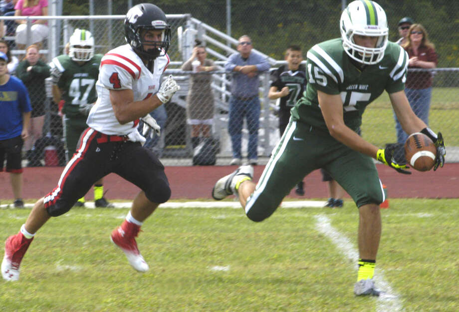 Green Wave senior Drew Hansen makes the catch on a pinpoint post pattern pass from NMHS quarterback Tyler Hansen before outrunning the Panther defense to the end zone  for a second-quarter touchdown Sunday afternoon at New Milford High School.  Photo: Norm Cummings