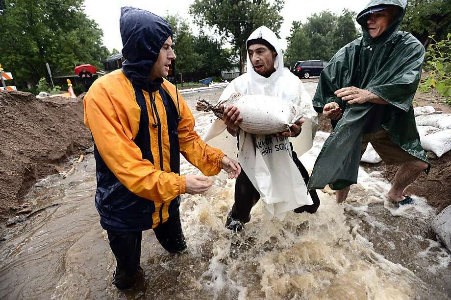 Dan Feldheim, left, Scott Hoffenberg, center, and John Smart, pass sandbags as residents reinforce the dam on University Hill in Boulder, Colo., on Sunday, Sept. 15, 2013. The National Weather Service says up to 2 inches of rain could fall Sunday, creating a risk of more flooding and mudslides.  (AP Photo/The Daily Camera, Paul Aiken) NO SALES Photo: Paul Aiken, Associated Press