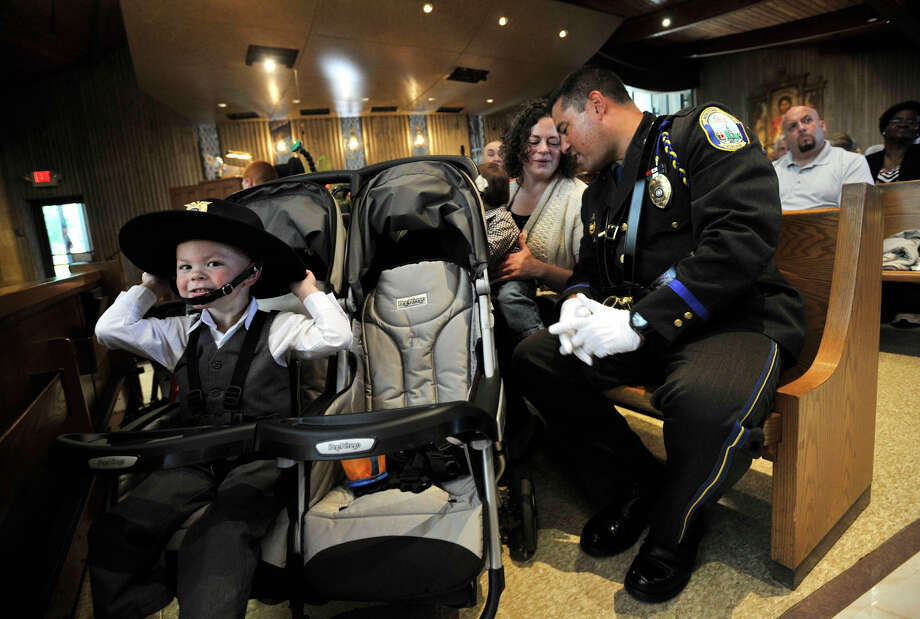 Joseph Monckton, 2, tries on his father's police hat as Newtown Police Officer Rich Monckton whispers to his wife, Cathy, during Blue Mass honoring first responders at St. Philip Church in Norwalk, Conn., on Sunday, Sept. 15, 2013. Photo: Jason Rearick / Stamford Advocate