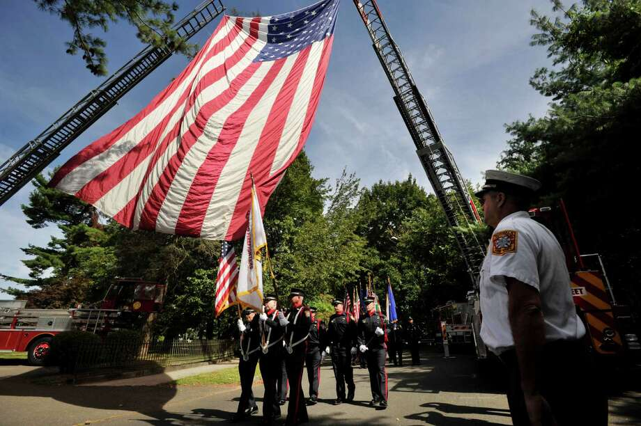 The delegation from the Stamford Fire Departmet pass underneath the American flag en route to the Blue Mass honoring first responders at St. Philip Church in Norwalk, Conn., on Sunday, Sept. 15, 2013. Photo: Jason Rearick / Stamford Advocate