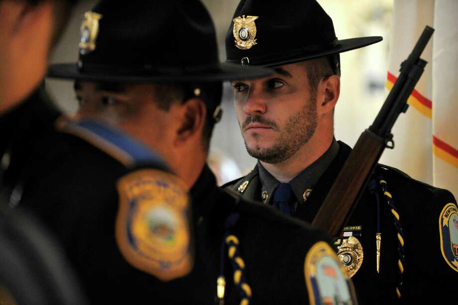 Newtown Police Officer Ben Muhall stands at attention before processing out near the end of the Blue Mass honoring first responders at St. Philip Church in Norwalk, Conn., on Sunday, Sept. 15, 2013. Photo: Jason Rearick / Stamford Advocate