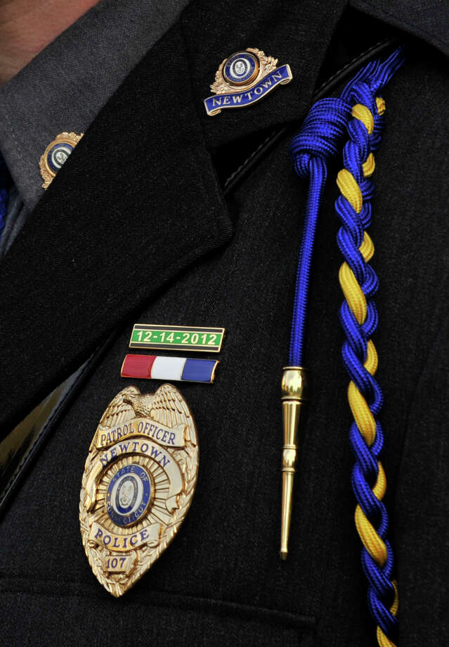Newtown Police Officer Ben Muhall has a pin with the date of the Sandy Hook Elementary School shooting above his badge during Blue Mass honoring first responders at St. Philip Church in Norwalk, Conn., on Sunday, Sept. 15, 2013. Photo: Jason Rearick / Stamford Advocate