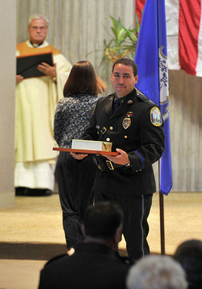 Newtown Police Officer Leonard Penna was given an award from St. Philip Church for his service during Blue Mass honoring first responders at the church in Norwalk, Conn., on Sunday, Sept. 15, 2013. Photo: Jason Rearick / Stamford Advocate