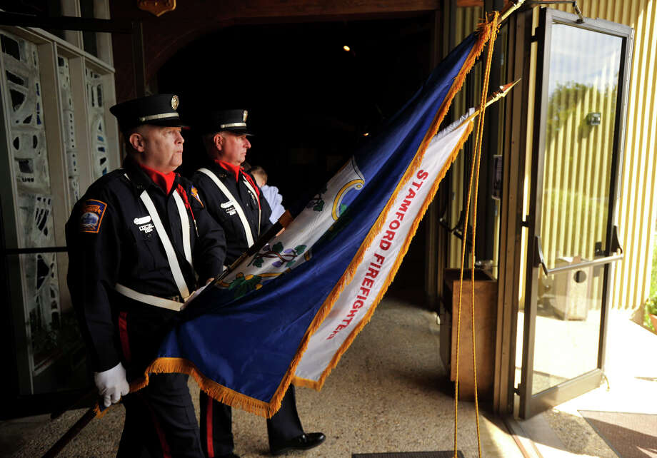 Retired firefighter Richard Gillespie, left, and Capt. Mark Shannon carry flags for the Stamford Fire Department at the end of Blue Mass honoring first responders at St. Philip Church in Norwalk, Conn., on Sunday, Sept. 15, 2013. Photo: Jason Rearick / Stamford Advocate