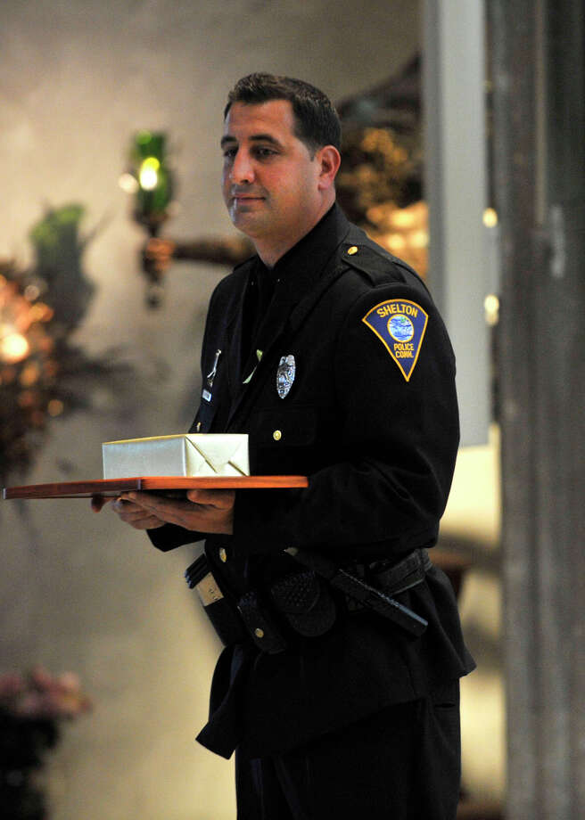 Shelton Police Officer Michael McPadden is given an award from St. Philip Church for his service during Blue Mass honoring first responders at the church in Norwalk, Conn., on Sunday, Sept. 15, 2013. Photo: Jason Rearick / Stamford Advocate