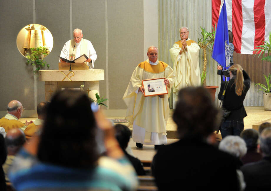 Monsignor Robert Weiss, of St. Rose of Lima Church in Newtown, is given a standing ovation after receiving an award for his service during Blue Mass honoring first responders at St. Philip Church in Norwalk, Conn., on Sunday, Sept. 15, 2013. Photo: Jason Rearick / Stamford Advocate