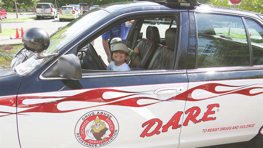 Nuri Hafizi, 5, of Westport, sits behind the wheel of the Fairfield Police Department's D.A.R.E. vehicle at the Junior Women's Club Touch-A-Truck event Sunday. Photo: Mike Lauterborn / Fairfield Citizen contributed