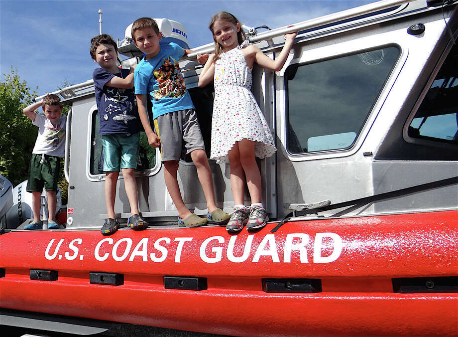 Brothers Caleb, Nathaniel and Sebastian Miller, ages 5, 9 and 8, with Isabel Poff, 7, check out a Coast Guard boat at the Junior Women's Club Touch-A-Truck event Sunday. Photo: Mike Lauterborn / Fairfield Citizen contributed