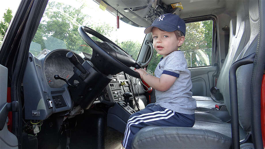 Michael Rodriguez, 2, in a front-end loader Sunday at Touch-A-Truck at Fairfield Ludlowe High School. Photo: Mike Lauterborn / Fairfield Citizen contributed