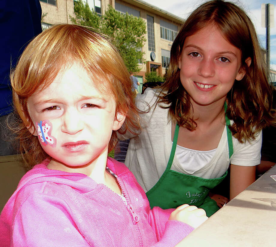 Dylan Deren, 3, sports face-painting designs by Caitlin May, 10, at the Touch-A-Truck event Sunday. Photo: Mike Lauterborn / Fairfield Citizen contributed