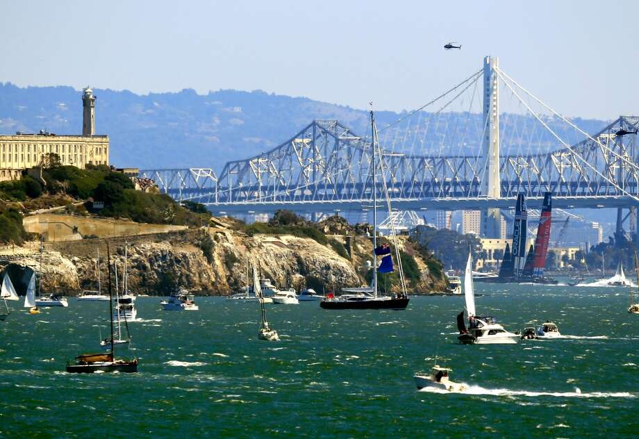 Emirates Team New Zealand and Oracle Team USA race in front of Alcatraz Island and the new Bay Bridge extension during race 9 of the America's Cup finals on September 15, 2013 in San Francisco, California. Photo: Jamie Squire, Getty Images