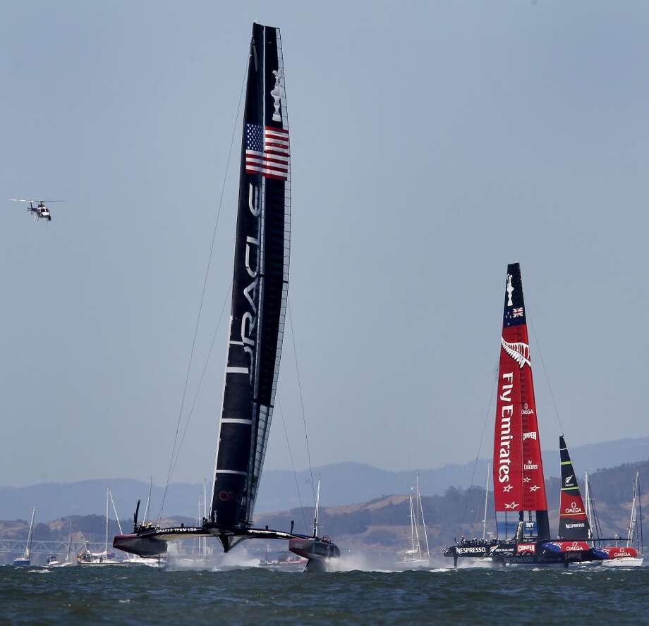 Oracle leads the Emirates boat near the finish line of race one Sunday September 15, 2013 in San Francisco, Calif. At the America's Cup park at Pier 27, hundreds of sailing fans watched the action between the United States and New Zealand. The Oracle team won the first race. Photo: Brant Ward, The Chronicle