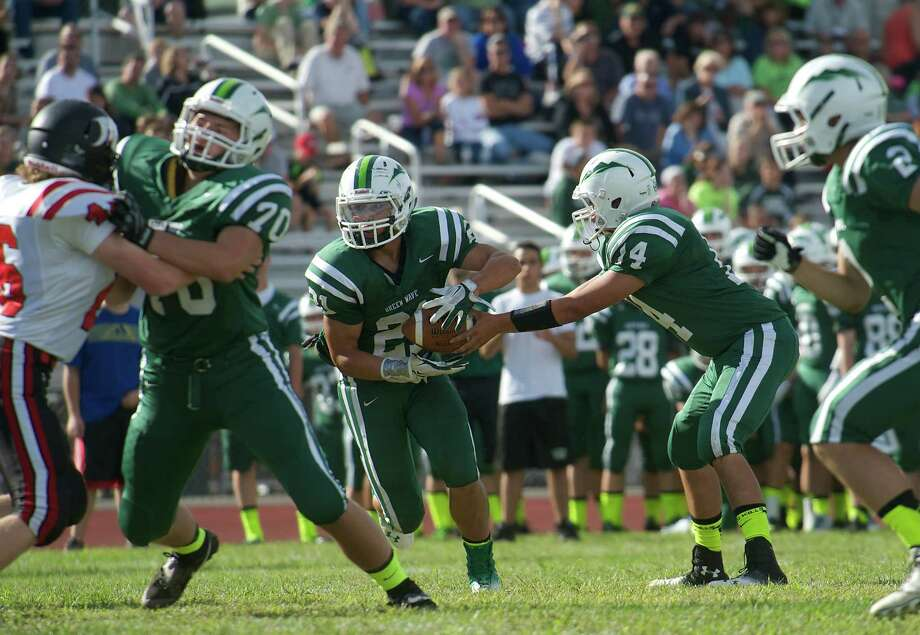 New Milford's AJ MacDonald, 21, takes a hand off from quarter back Tyler Hansen, 14, during Sundays football game against Masuk High School at New Milford High School on September 15, 2013. Photo: H John Voorhees III
