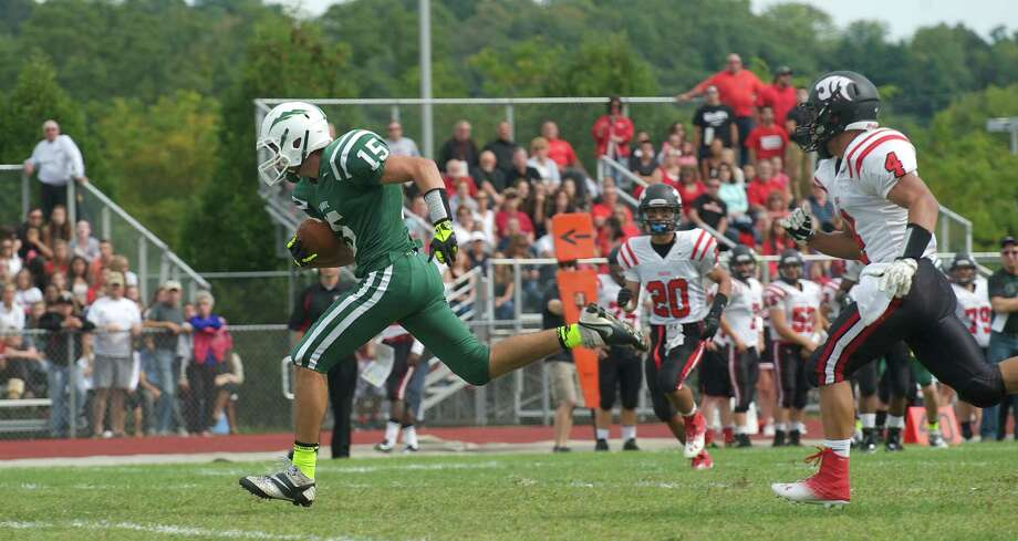 New Milford wide receiver Drew Hanson, 15, races away from Masuk's Mike Dellapiano, 4, for a touch down during Sundays football game against Masuk High School at New Milford High School on September 15, 2013. Photo: H John Voorhees III
