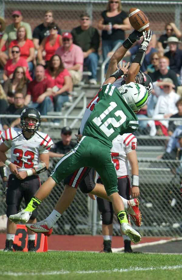 New Milford's Robert Sherry, 12, knocks away a pass to Masuk's Russell Lilly, 19, during Sundays football game against Masuk High School at New Milford High School on September 15, 2013. Photo: H John Voorhees III