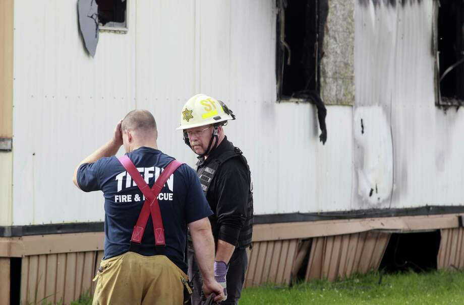 Wm. Timothy Spradlin, chief of the Fire and Explosion Investigation Bureau, right, speaks with a member of the Tiffin Fire and Rescue, left, during the investigation into the scene of a fire that killed five children and one adult on Sunday, Sept. 15, 2013, in Tiffin, Ohio. The fire was reported shortly before 8 a.m. Sunday in a mobile home park in Tiffin, about 50 miles southeast of Toledo, Ohio. (AP Photo/The Blade, Amy Voigt) Photo: Amy E. Voigt, Associated Press / The Blade