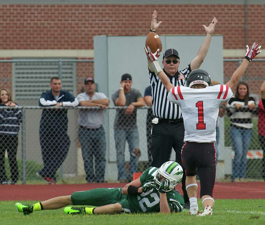 Head Linesman Brian Juglar agrees with Masuk wide receiver Robert Keene,1, and signals a touch down during Sundays football game against Masuk High School at New Milford High School on September 15, 2013. New Milford's Michael Zigmantanis looks on. Photo: H John Voorhees III
