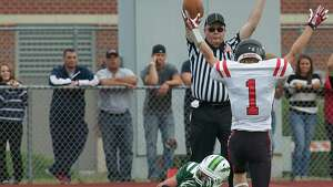 Head Linesman Brian Juglar agrees with Masuk wide receiver Robert Keene,1, and signals a touch down during Sundays football game against Masuk High School at New Milford High School on September 15, 2013. New Milford's Michael Zigmantanis looks on.
