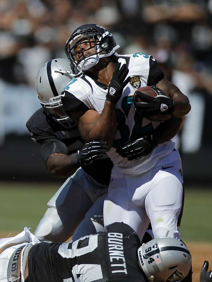 Sio Moore (left) and Kevin Burnett bring down Maurice Jones-Drew, who left the game with an ankle injury. Photo: Carlos Avila Gonzalez, The Chronicle