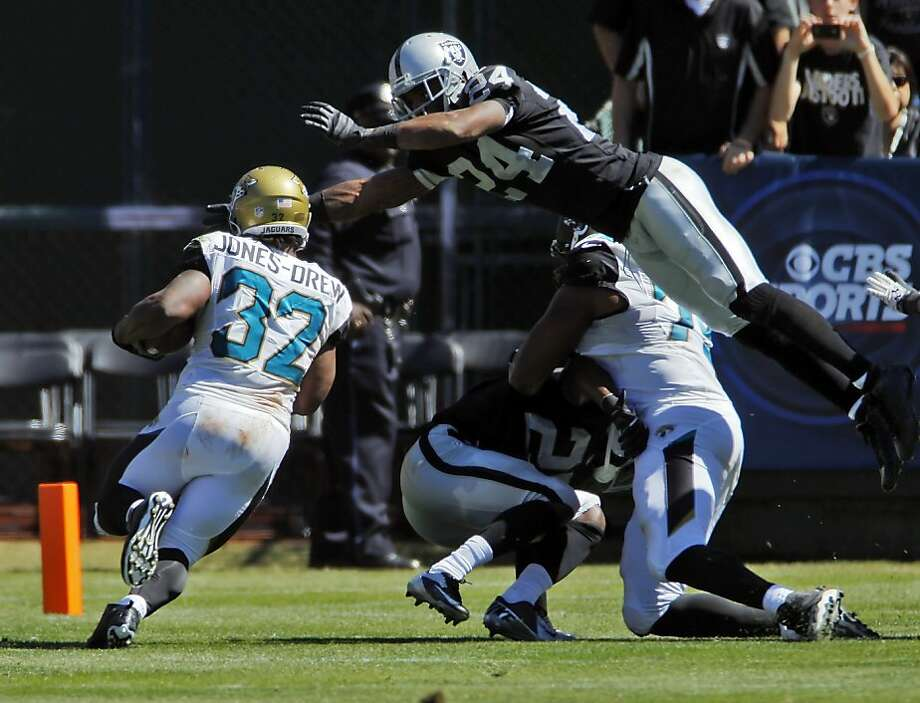 Charles Woodson leaps tall blockers in a single bound to stop the Jags' Maurice Jones-Drew. Photo: Carlos Avila Gonzalez, The Chronicle
