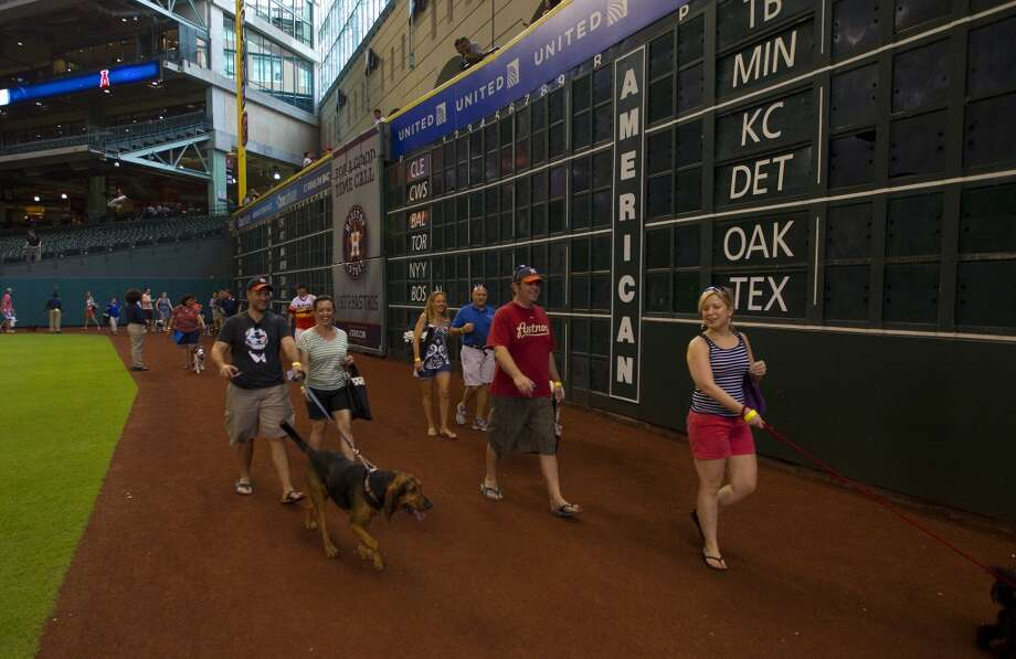 Participants walk the warning track during the Pooch Parade. Photo: Cody Duty, Chronicle
