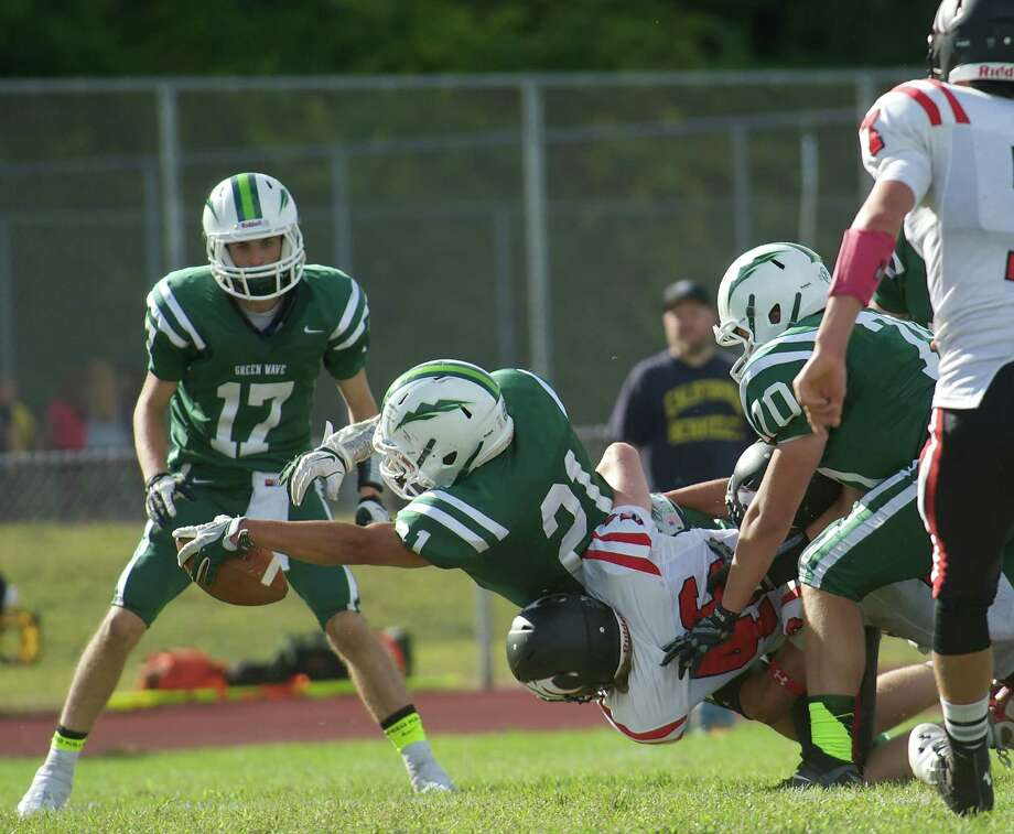 New Milford's AJ MacDonald, 21, stretches over the goal line to score a touch down during Sundays football game against Masuk High School at New Milford High School on September 15, 2013. Photo: H John Voorhees III