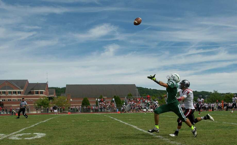 New Milford's Drew Hansen, 15, reaches for a pass while Masuk's number 7defends during Sundays football game against Masuk High School at New Milford High School on September 15, 2013. Photo: H John Voorhees III