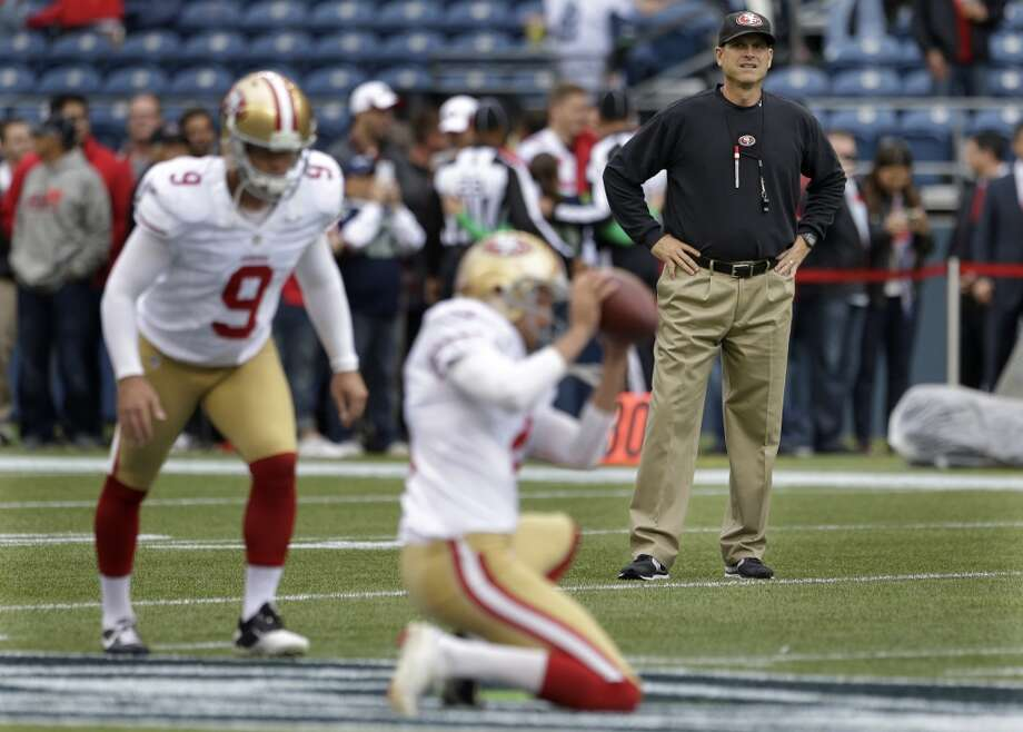 San Francisco 49ers head coach Jim Harbaugh, right, watches as San Francisco 49ers kicker Phil Dawson (9) and holder Andy Lee warm up. Photo: Elaine Thompson, Associated Press