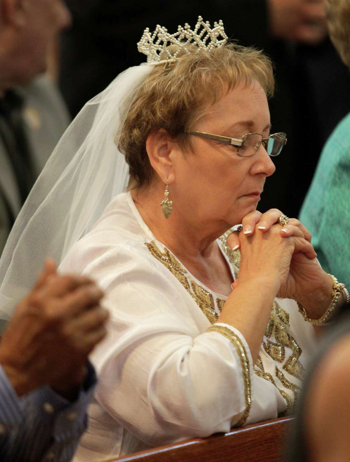 Lynnette Bartula of Houston wearing her orginal wedding headpiece prays during the Wedding Anniversary Jubilee at the Co-Cathedral of the Sacred Heart, 1111 St. Joseph Pkwy., Sunday, Sept. 15, 2013, in Houston. She and her husband, Ray Bartula, who were married on Sept. 17, 1963, joined more than 250 other couples in a mass lead by Cardinal Daniel DiNardo honoring couples celebrating their 50th wedding anniversary. The headpiece is original but she and her daughter, Dena Tamborella, had to replace the veil material.