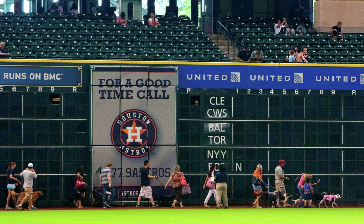 Participants walk the warning track during the Pooch Parade during Dog Day at Minute Maid Park Sunday, Sept. 15, 2013, in Houston.