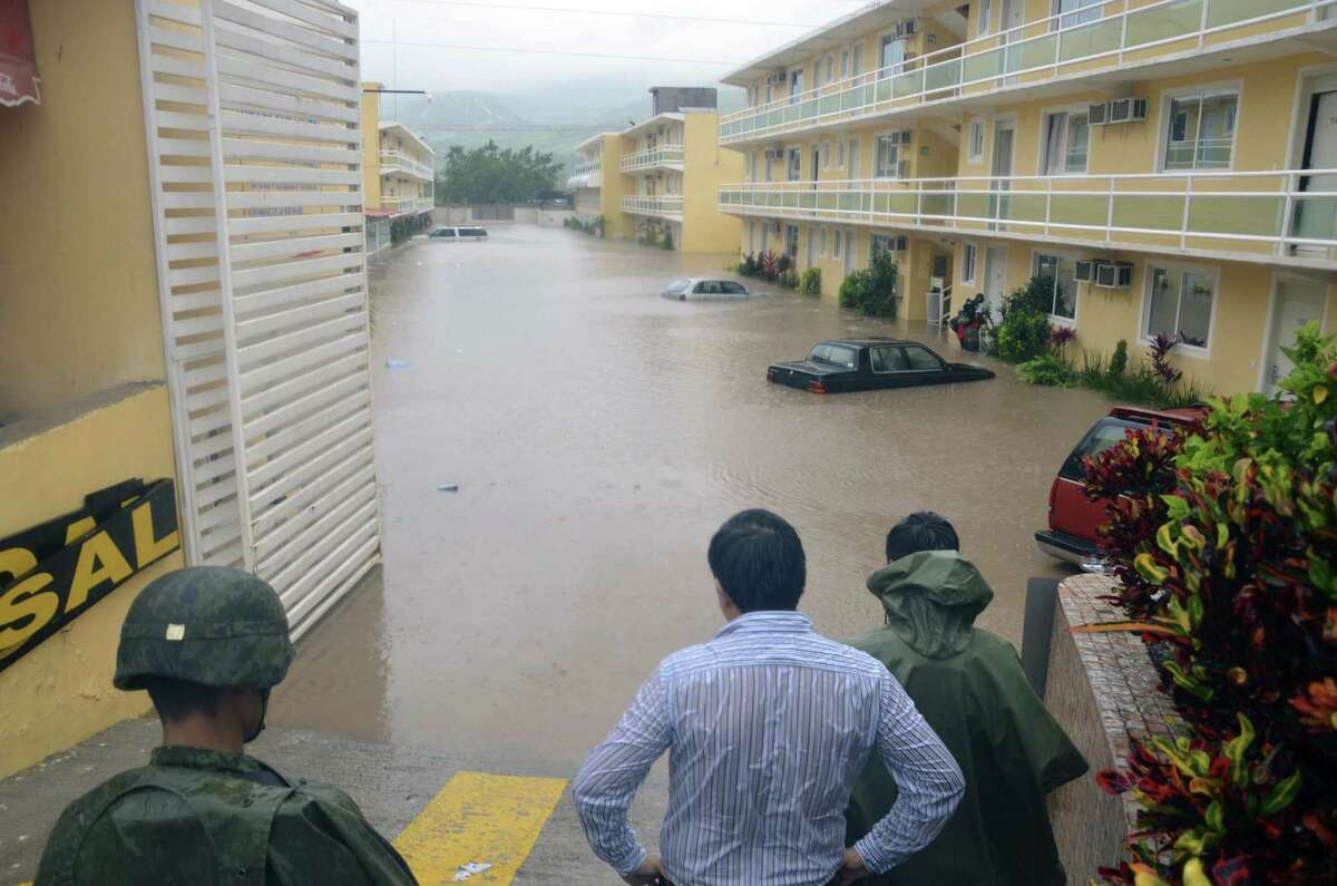 Army soldiers and a civilian look out into a flooded street in the city of Chilpancingo, Mexico. Tropical Storm Manuel weakened as soon as it made landfall but brought torrential rain.