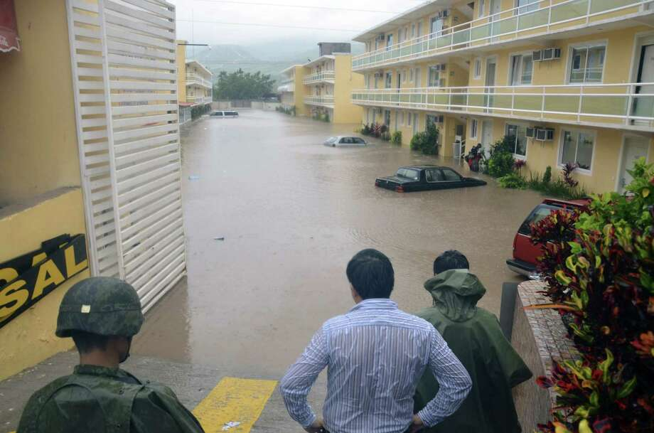Army soldiers and a civilian look out into a flooded street in the city of Chilpancingo, Mexico. Tropical Storm Manuel weakened as soon as it made landfall but brought torrential rain. Photo: Alejandrino Gonzalez / Associated Press
