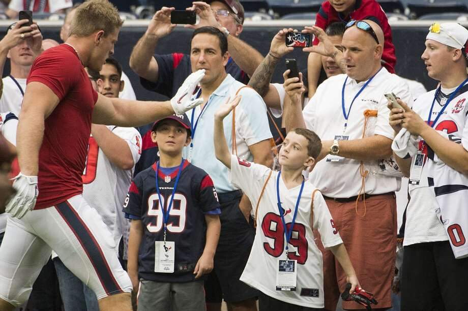 Defensive end J.J. Watt high fives a young fan. Photo: Smiley N. Pool, Chronicle